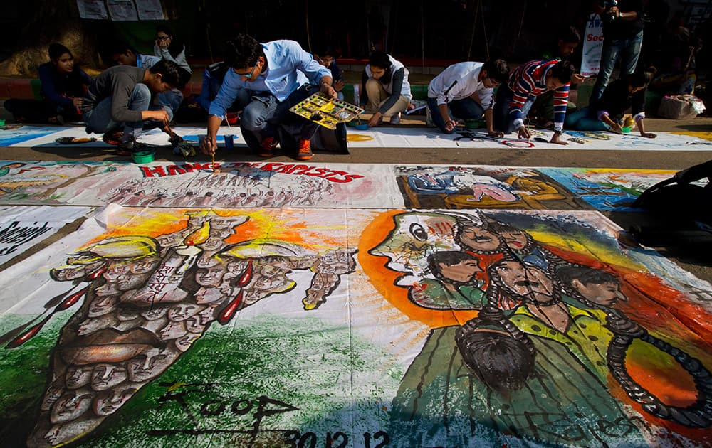 Indian students make paintings to vent out their anger on the lack of measures taken to ensure safety of women as they pay respect on the second anniversary of the deadly gang rape of a student on a bus, in New Delhi, India.