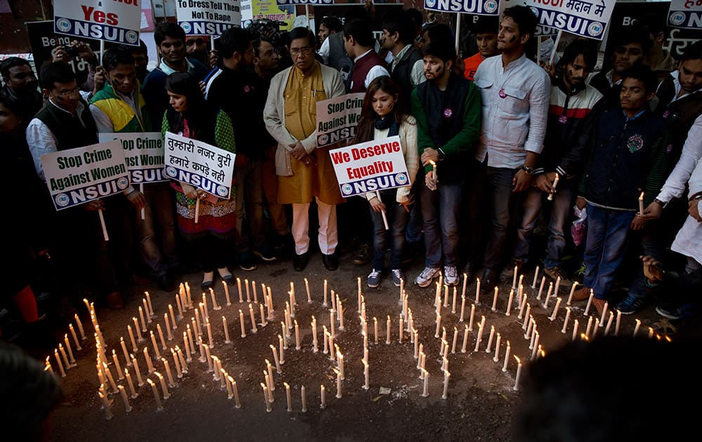 Members of India's Congress party's students' wing hold placards and light candles on the eve of the second anniversary of the deadly gang rape of a student on a bus, in New Delhi, India.