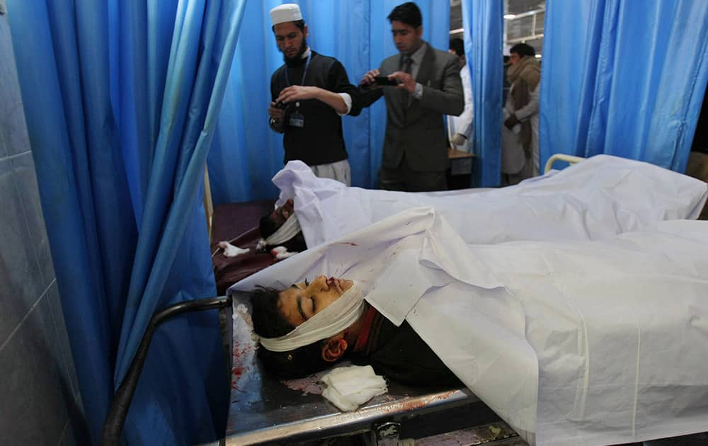 Pakistanis use their mobile phones to take photographs of students who died in a Taliban attack on their school, at a local hospital in Peshawar, Pakistan.