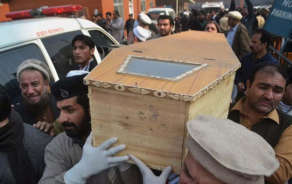 People carry the casket of a victim of Taliban attack in a school, after receiving it from a local hospital in Peshawar, Pakistan.