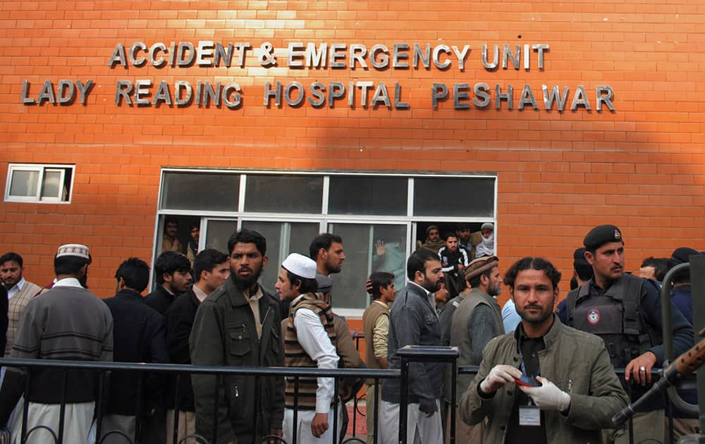 People gather at a hospital, where victims of a Taliban attack are being treated in Peshawar, Pakistan.