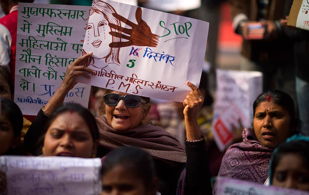 Women raise slogans against the dearth of reforms and steps taken to ensure women's safety on the second anniversary of the deadly gang rape of a student on a bus, in New Delhi, India.The placard shows Dec. 16 replaced by Dec. 5 referring to the Dec. 5 accusation of rape on an Uber radio taxi driver.