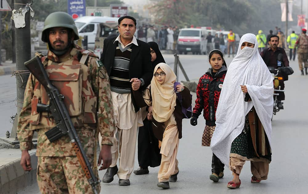Pakistani parents escort their children outside a school attacked by the Taliban in Peshawar, Pakistan.