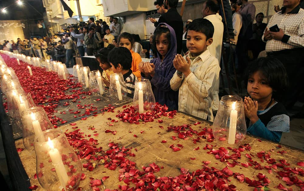 Pakistani children, chant prayers, during a candle light vigil for the victims of a Taliban attack on a school in Peshawar, organized by supporters of the Mutahida Qaumi Movement (MQM), in Karachi, Pakistan.