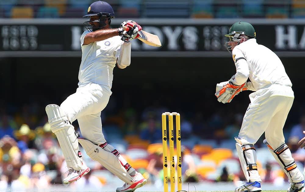 Indian batsman Cheteshwar Pujara plays a pull shot as Australia's Brad Haddin, right, looks on during the second cricket test in Brisbane, Australia.