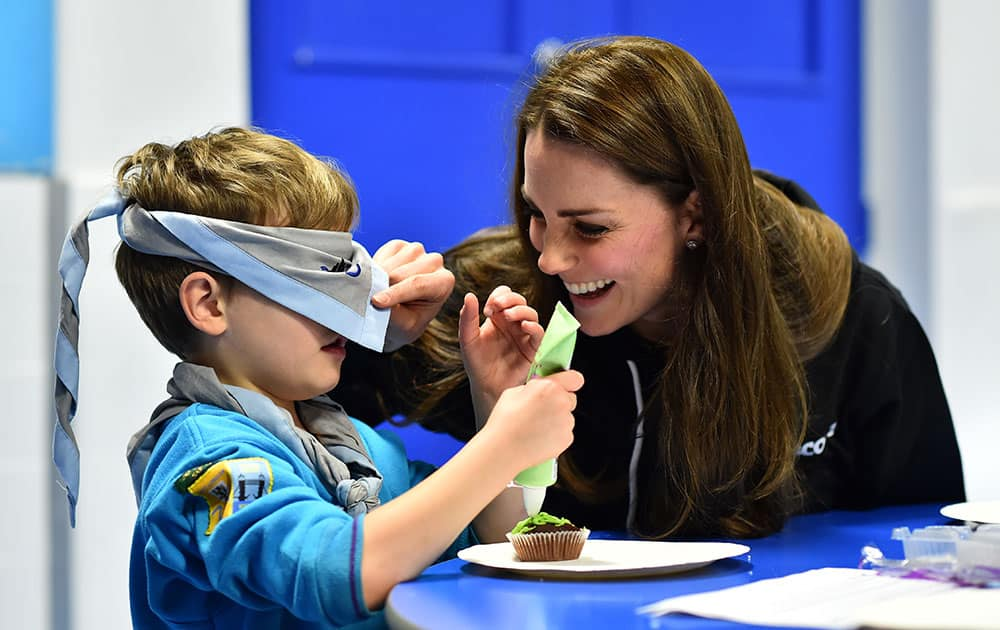 Britain's Kate, Duchess of Cambridge checks the blindfold of Fynley Gooch, 7, before helping him ice a cake as she promotes disability awareness as she meets with children at the newly established 23rd Poplar Beaver Scout Colony in east London.