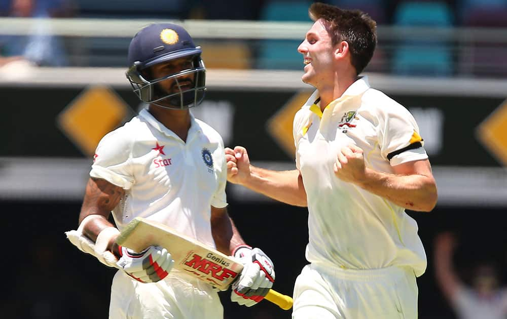 Australia's Mitchell Marsh celebrates after taking the wicket of India's Shikhar Dhawan, left, during the second cricket test match between Australia and India in Brisbane, Australia.
