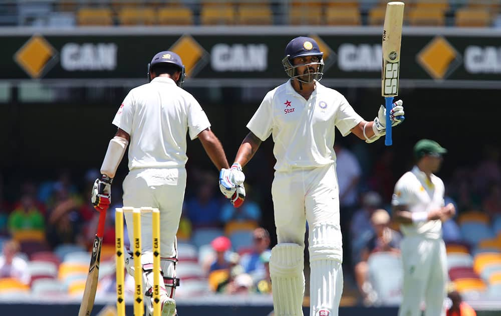 India's Murali Vijay waves his bat after scoring a half century during the second cricket test match against Australia in Brisbane, Australia.