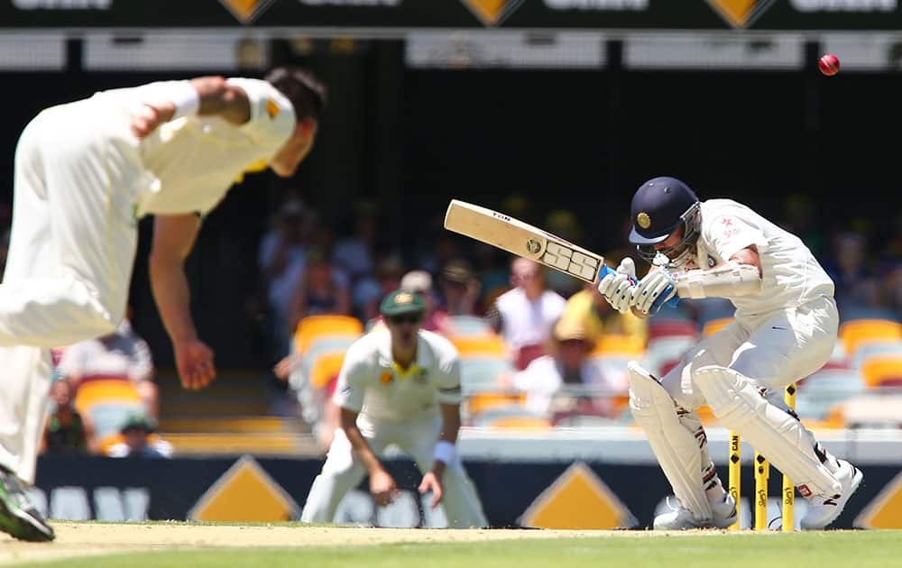 India's Murali Vijay ducks under a bouncer from Australia's Mitchell Johnson, left, during the second cricket test match between Australia and India in Brisbane, Australia.