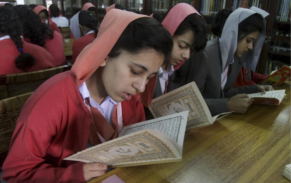 Pakistani students recite holy book 'Quran' during a praying ceremony for the victims of Tuesday's school attack in Peshawar, at a school in Lahore, Pakistan.