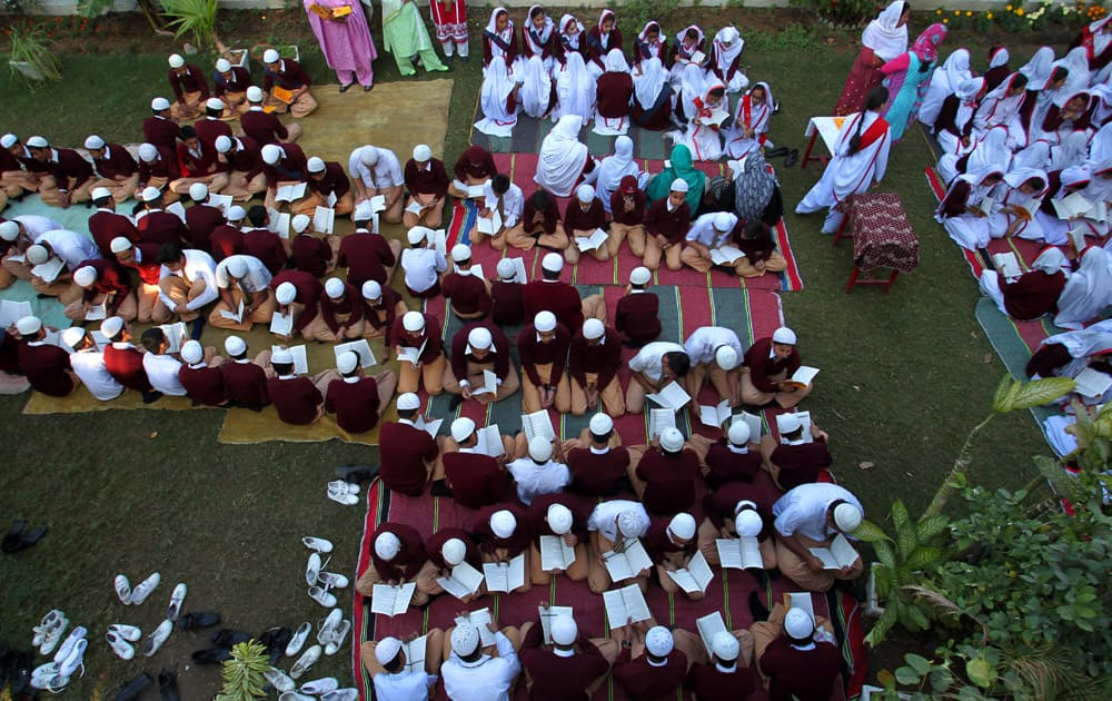 Pakistani students recite holy book 'Quran' during a praying ceremony for the victims of Tuesday's school attack, at a school in Karachi, Pakistan.