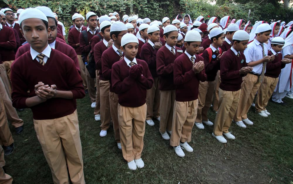 Pakistani students pray during a ceremony for the victims of Tuesday's school attack, at a school in Karachi, Pakistan.
