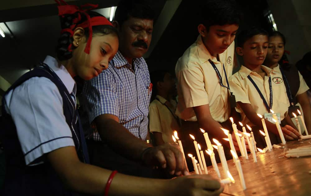 India school children and officials light candles in memory of victims killed in a Taliban attack on a military-run school in Peshawar, at a school in Mumbai, India.