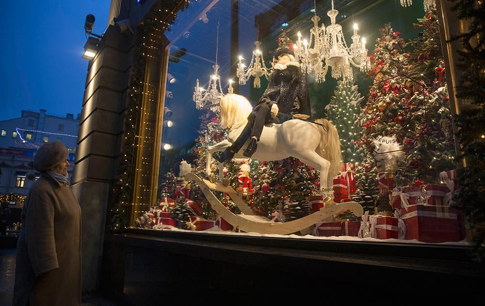 An elderly woman looks at a decorated for Christmas shop window of the Central Department Store in downtown Moscow, Russia.