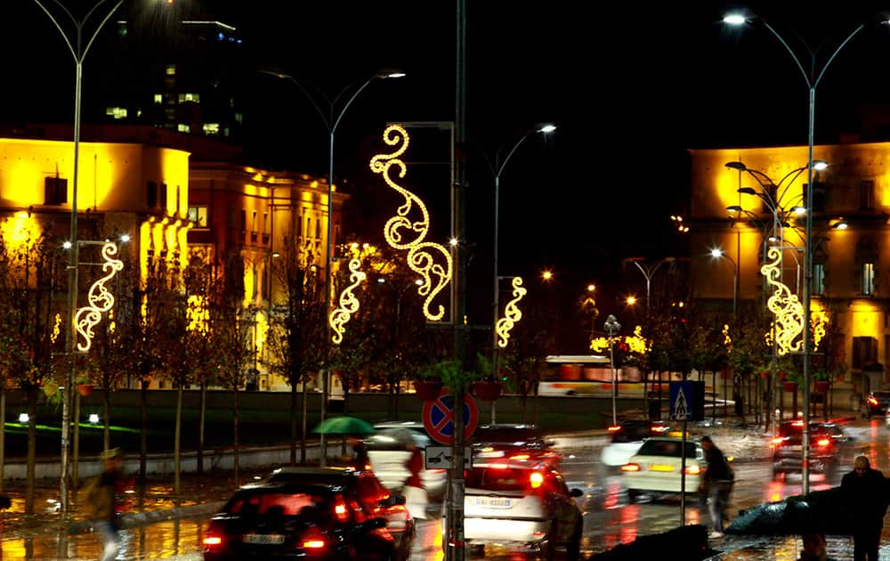 Pedestrians cross the road at Albania's capital main Skanderbeg Square decorated ahead of the Christmas and New Year festivities, both considered as the most popular holidays in the post-communist country, in Tirana, Albania.