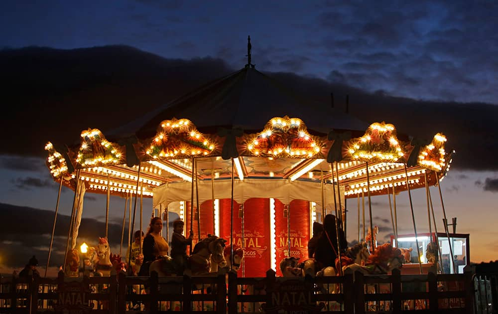 People ride on a carousel in a Christmas market at the Comercio square, in Lisbon, Portugal.