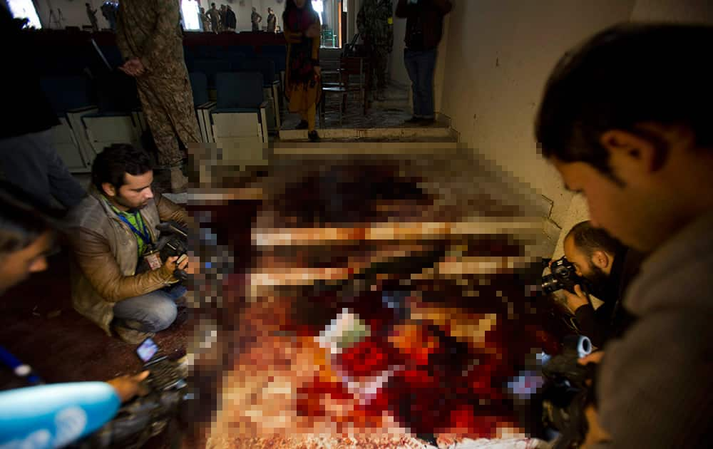 Pakistani journalists film and photograph inside an auditorium of the Army Public School attacked the day before by Taliban gunmen, in Peshawar, Pakistan.