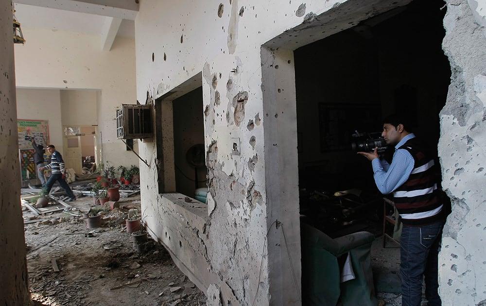 A Pakistani journalist films inside the Army Public School attacked the day before by Taliban gunmen in Peshawar, Pakistan.
