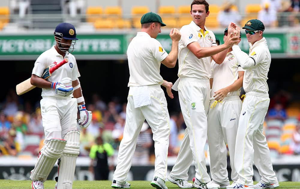 Australia's Josh Hazlewood is congratulated by teammates after taking the wicket of India's Ajinkya Rahane, left, during play on day two of the second cricket test in Brisbane, Australia.