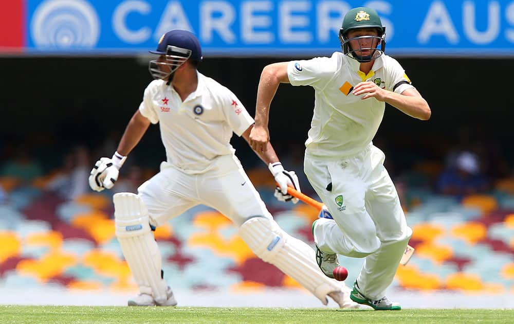 Australian fielder Chris Rogers runs after the ball played by India's MS Dhoni during play on day two of the second cricket test in Brisbane, Australia.