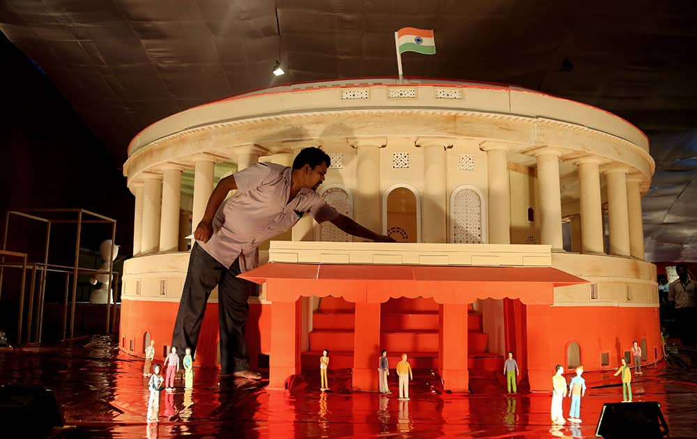 A worker touches a cake made in the shape of Indian parliament building on display at the annual cake show as part of new year celebrations in Bangalore, India.  The cake measures 18 feet in diameter and is made of about 5000 kilogram (11,023 pounds) of sugar, eggs and cornflour, claimed the maker.