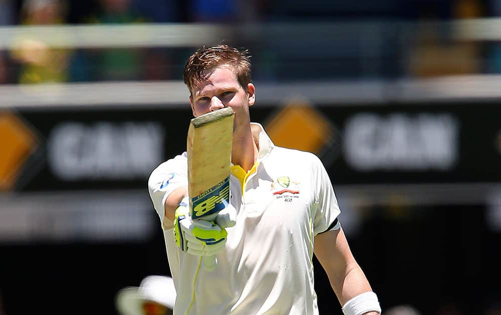 Steven Smith points his bat after hitting a century on the third day of the second cricket test against India in Brisbane, Australia.