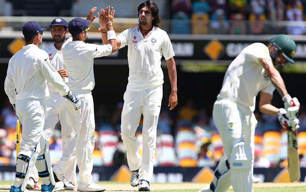 Ishant Sharma celebrates with his team after getting the wicket of Australia's Mitchell Johnson, on the third day of the second cricket test in Brisbane, Australia.