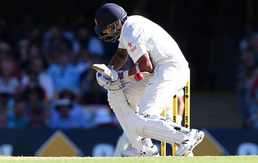 Murali Vijay reacts after being hit by the ball during play on day three of the second cricket test between Australia and India in Brisbane, Australia.