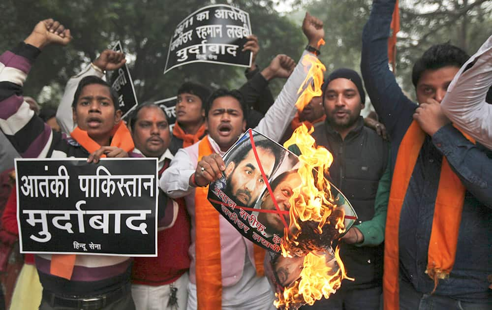 A small group of rightwing activists of the Hindu Sena or the Hindu Army burn posters with portraits of Pakistani Prime Minister Nawaz Sharif and Zaki-ur-Rehman Lakhvi, the chief suspect in the Mumbai attack trial, near the residence of Pakistan High commissioner to India in New Delhi.