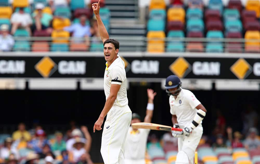Australia's Mitchell Starc, celebrates after getting the wicket of Ravichandaran Ashwin, during their play on day four of the second cricket test in Brisbane, Australia.