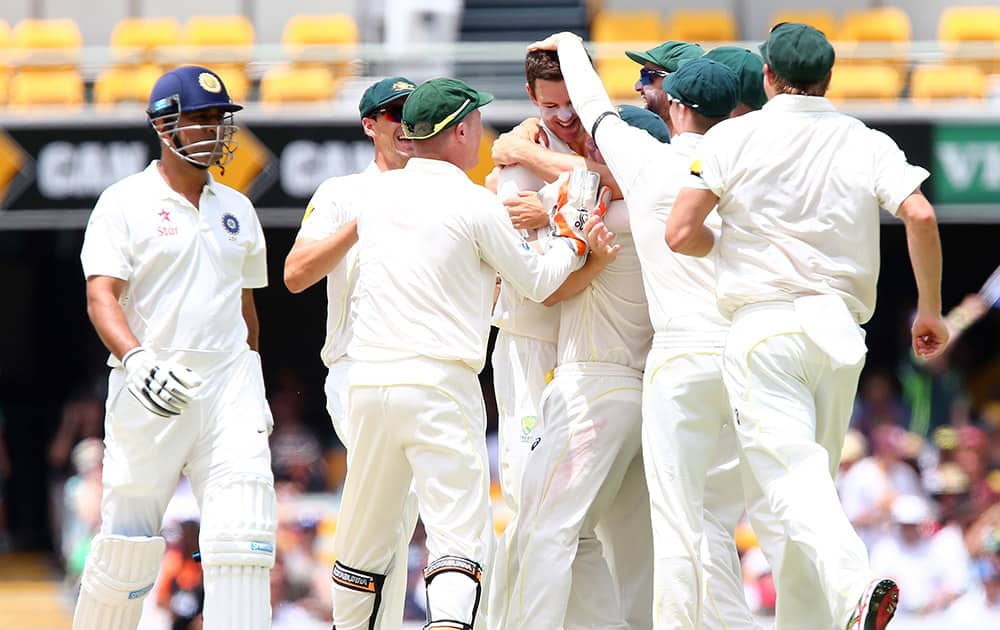 Australia's Josh Hazlewood, celebrates with his teammates after getting the wicket of MS Dhoni, at their play on day four of the second cricket test in Brisbane, Australia.