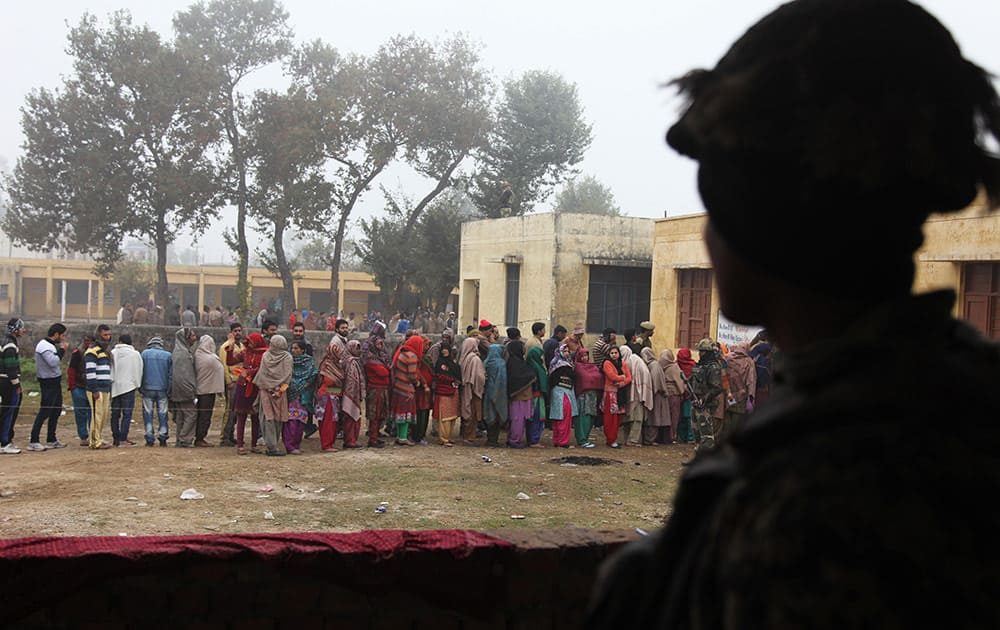 Paramilitary soldiers stand guard, as people stand in queues to cast their votes outside a polling station during the fifth phase of voting, at Satrayan village, Jammu.