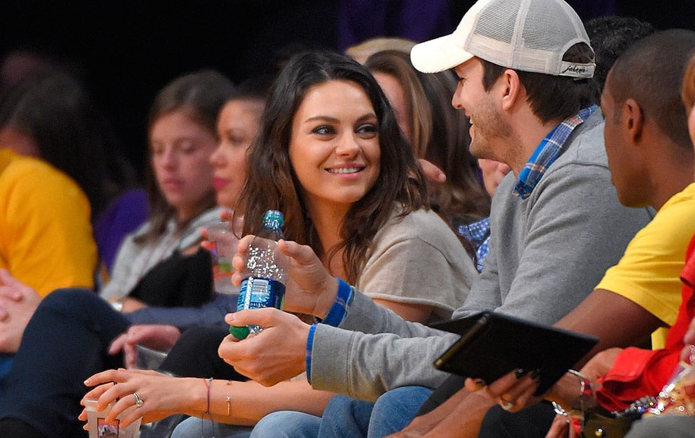 Actors Mila Kunis and Ashton Kutcher watch the Los Angeles Lakers play the Oklahoma City Thunder in an NBA basketball game, in Los Angeles.