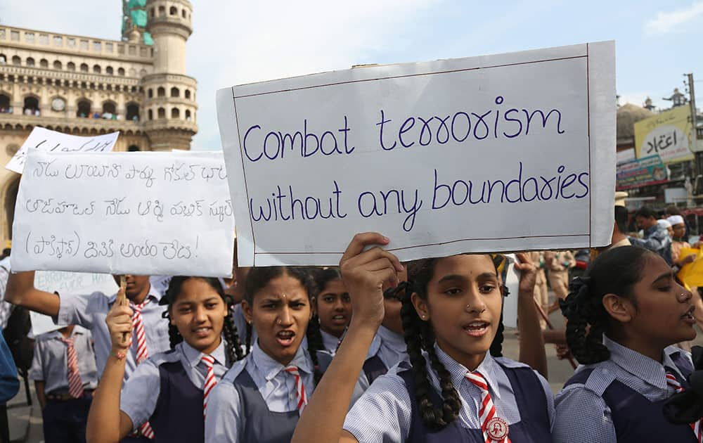 Schoolgirls hold placards during a rally to pay homage to victims of Tuesday's Taliban attack on a military-run school in Peshawar, in Hyderabad.