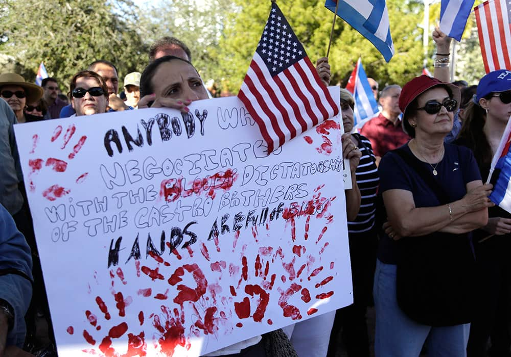 Sonia San Martin holds a sign during a protest in the Little Havana neighborhood of Miami against President Barack Obama's plan to normalize relations with Cuba.