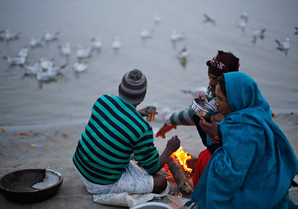Indian street vendors keep warm around a bonfire on a cold evening on the banks of the River Ganges in Allahabad.