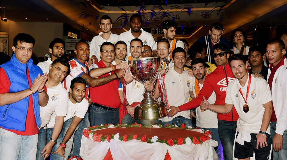 Players of Atletico De Kolkata Football team alongwith with teams their co-owners, Sourav Ganguly, Sanjiv Goenka poses with the Trophy after they arrive in Kolkata.