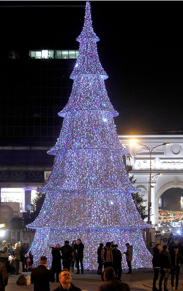 People stand near the illuminated Christmas tree set on the main square in Macedonia's capital Skopje.