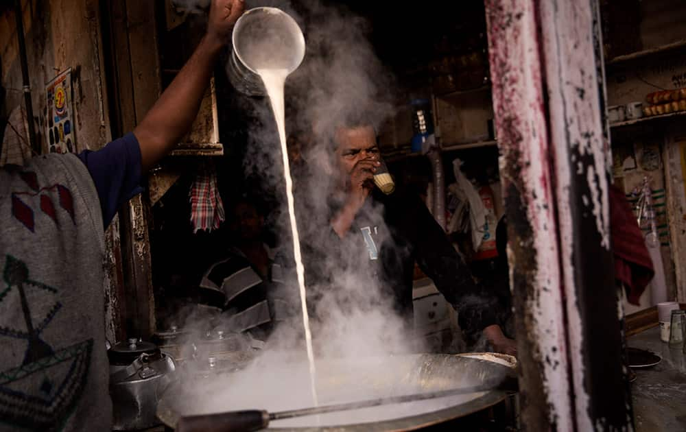An Indian man pours milk into a huge pot to prepare tea at a roadside stall in old parts of New Delhi.