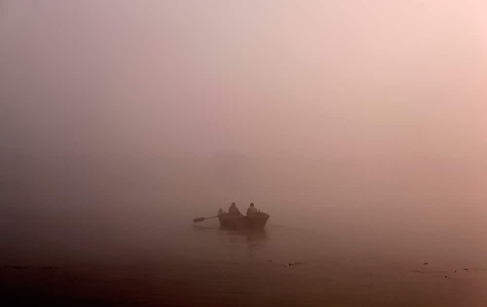 A man rows his boat on the River Ganges in the early morning fog on the outskirts of Allahabad.