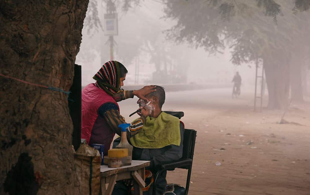 An Indian man gets a shave on a cold morning, at Allahabad, India, Monday.