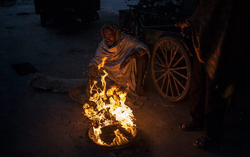 Indian men stay warm near a fire in New Delhi, India, Monday.