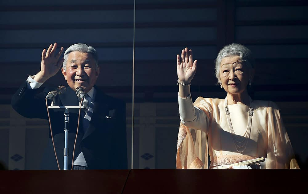 Japan's Emperor Akihito, accompanied by his wife Empress Michiko, wave at well-wishers as they appear on the balcony of the Imperial Palace to mark the emperor's 81th birthday in Tokyo.