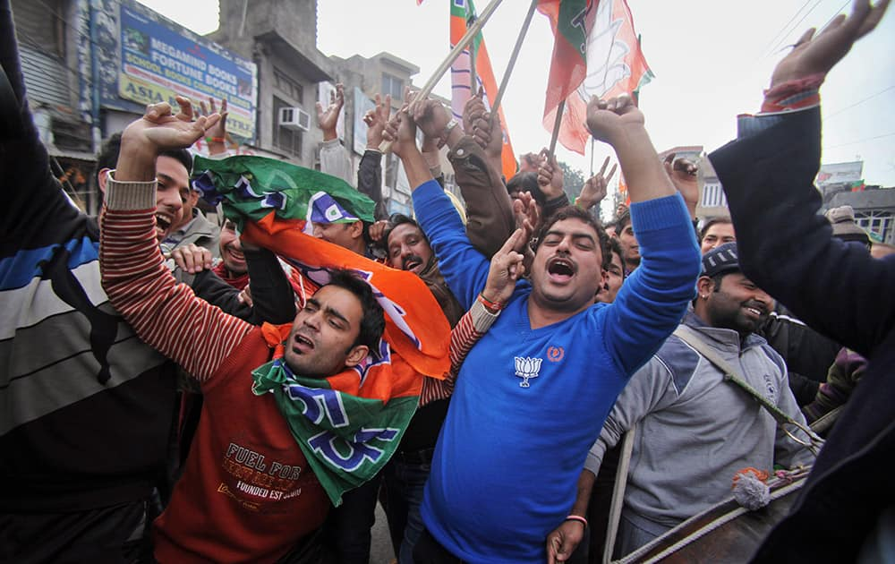 BJP supporters dance to celebrate the news of early election result trends outside their party headquarters in Jammu.