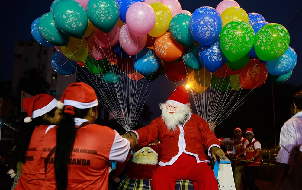 A man dressed as Santa Claus distributes candy, seated on a horse cart during a Christmas carnival in Mumbai.