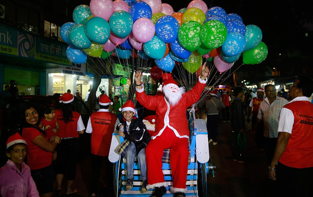 A man dressed as Santa Claus sits on a horse cart with a child during a Christmas carnival in Mumbai.