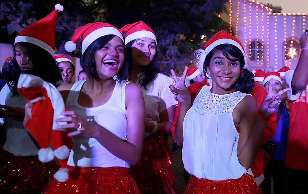 Girls wear Santa Claus hats and pose for a photograph during a Christmas carnival in Mumbai.