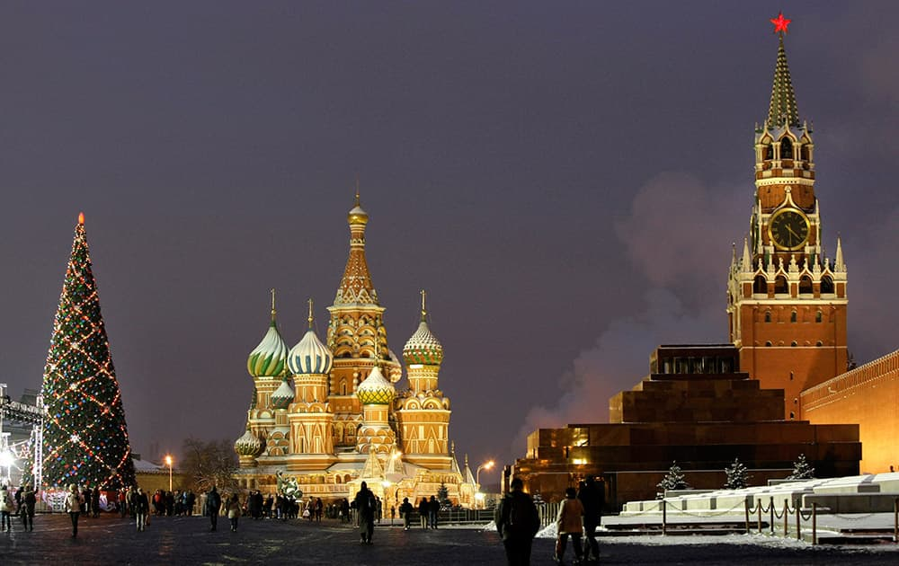 Christmas tree installed in Red Square, with St. Basil Cathedral, the Kremlin's Spassky Tower and Lenin Mausoleum, in Moscow, Russia.