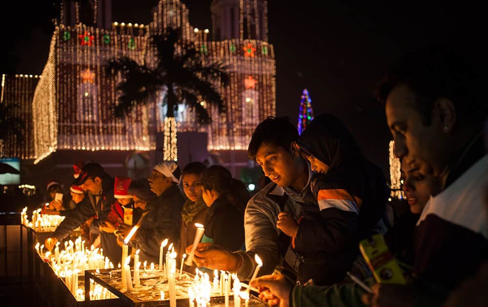 Christians light candles at a Sacred Heart Cathedral on the eve of Christmas in New Delhi.