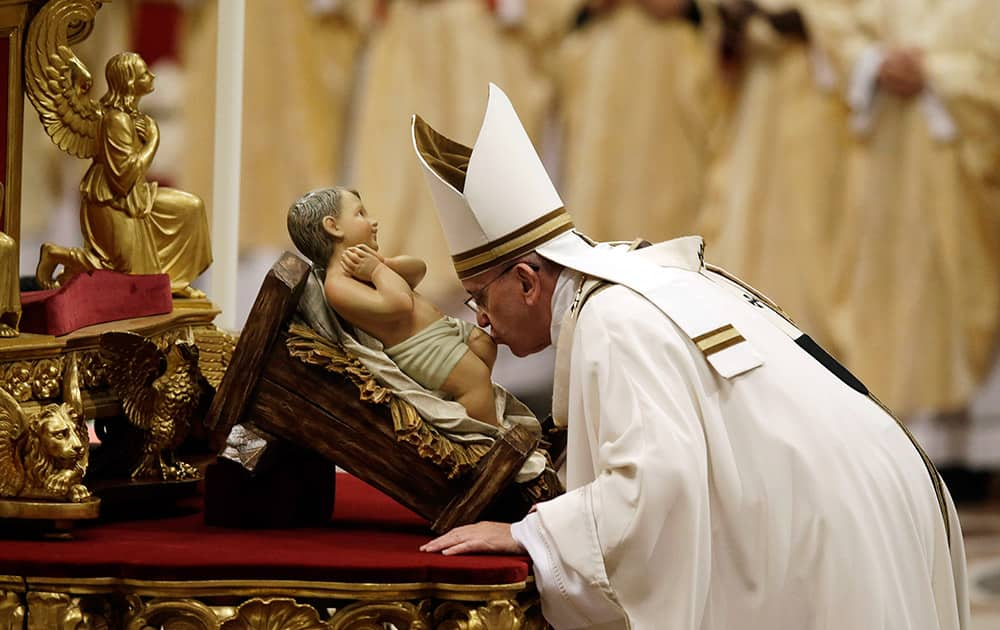 Pope Francis kisses a statue of Baby Jesus as he celebrates the Christmas Eve Mass in St. Peter's Basilica at the Vatican.